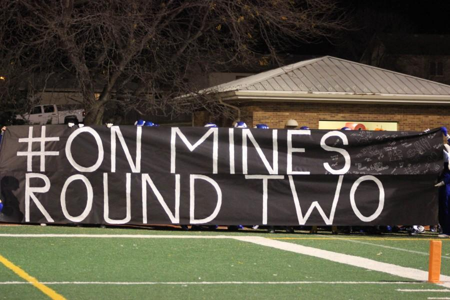 Cheerleaders+hold+up+the+banner+for+the+football+players.++%22On+Mines%22+is+a+phrase+from+number+4%2C+Jordan+Strong.