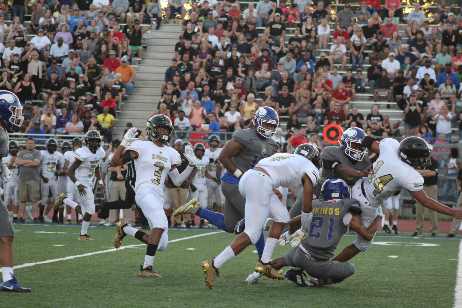 """Tyree Stovall, 12, number 21, tackles Omaha Burke's number 14 on September 14. Stovall has only had Luedtke as a coach for a year but he really likes his coaching style. """"He keeps you motivated and works just as hard as anyone else,"""" Stovall said. Photo by Gabby Push"""