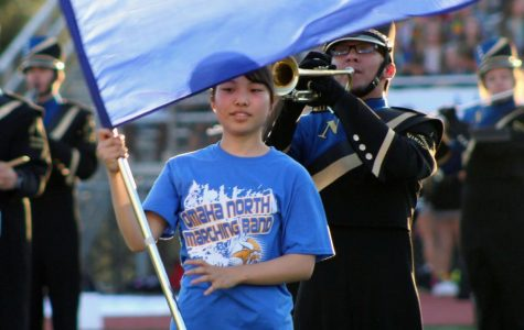 Junna Nozaki, 12, holds the flag for color guard at the North vs. Burke football game on September 14, 2018. Japan does not have color guard or football, so these are new experiences for Nozaki. Photo by Caitlin Pieters
