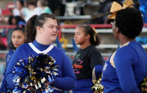Sparkle cheerleader cheers at the homecoming game. The sparkles wear blue and gold to show their school spirit. Photo by Caitlin Pieters