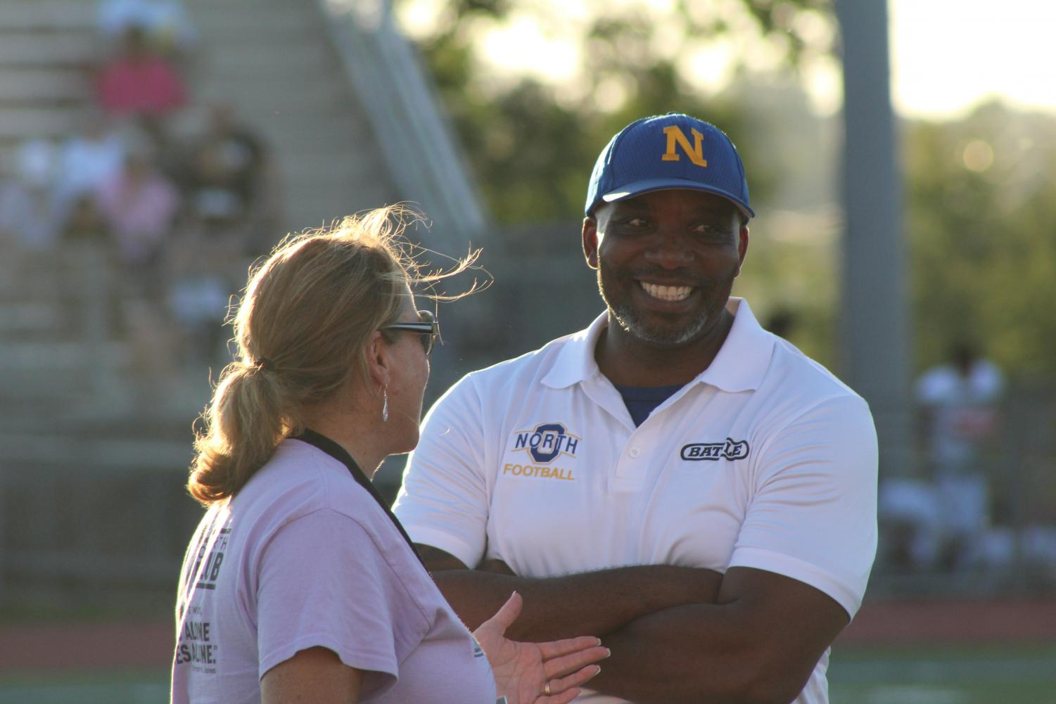 Johnson laughs on the sidelines of the varsity football game against Burke with co-worker Melinda Bailey.