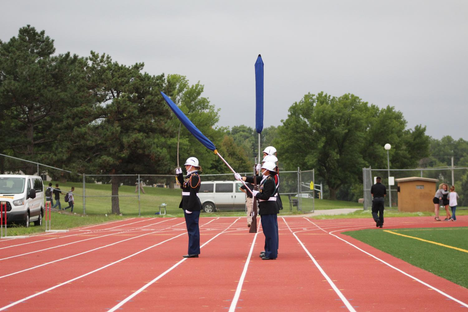 "Omaha North High's JROTC Color Gurad honors America during ""The Star Spangled Banner."" The flags were covered becuase of the rain.  Photo by Caitlin Pieters"