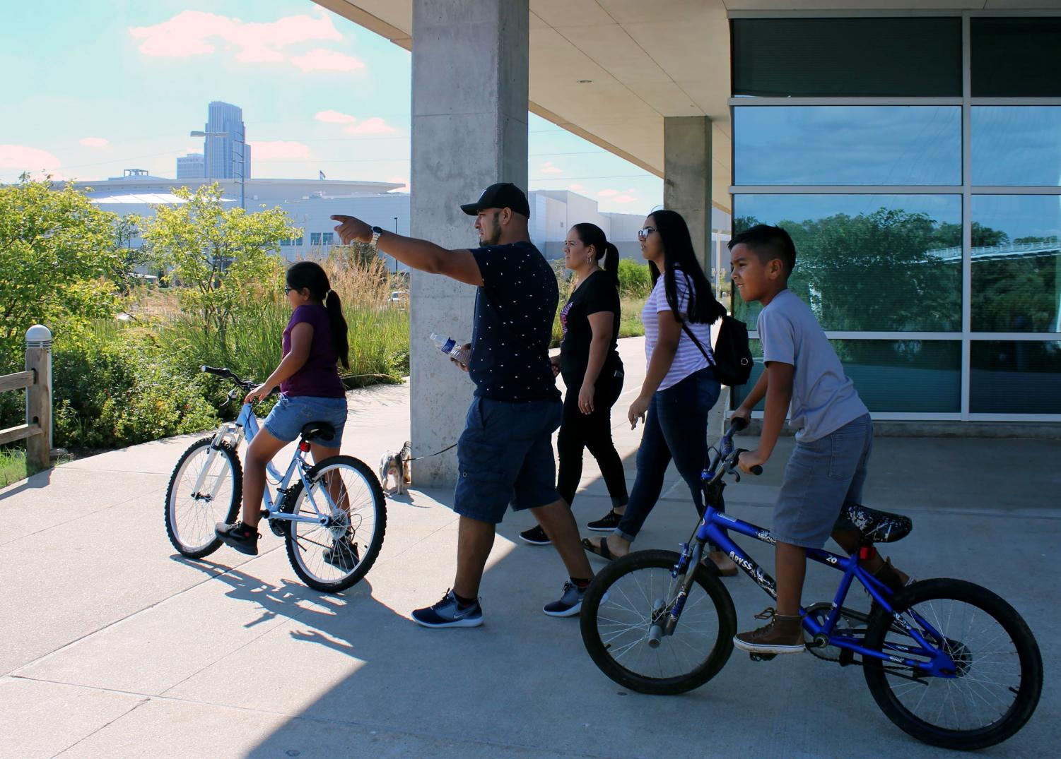 Kasandra Fuertes and her family walk downtown near the Bob Kerrey Pedestrian Bridge on Sept. 9, 2018, spending quality time together. Her father, Jose Fuertes, pointed at the water that flooded the river banks. Photo by Joseline Albeño