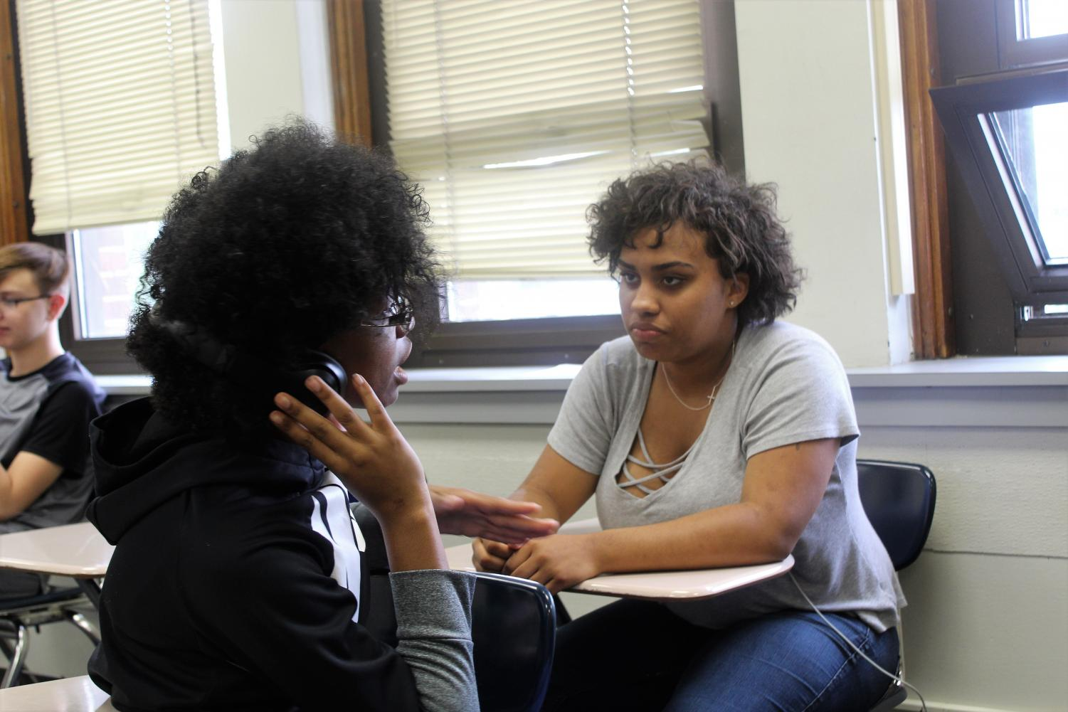 Two students work together to go over their Speech and Debate pieces. Photo by Emily Mann