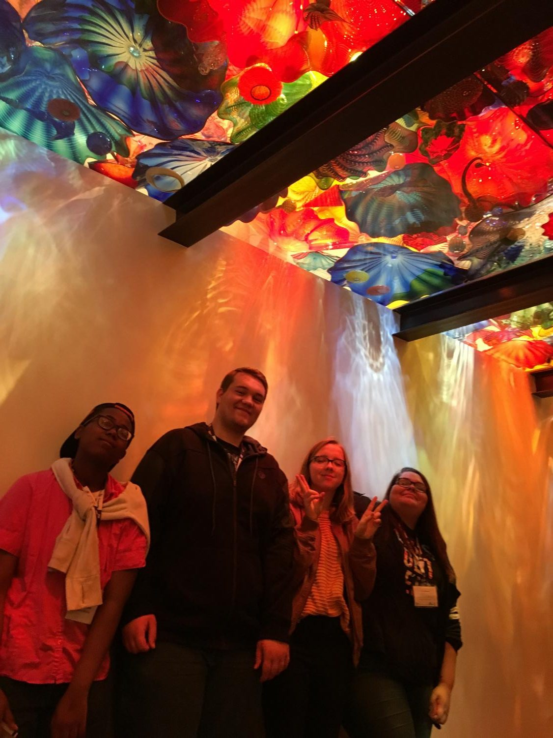 On Mar. 24, 2018, National Art Honors Society members visited the Chihuly Garden and Glass art museum while in Seattle Washington. Above the students sits multiple colorful glass sculptures, made by Dale Chihuly, with lights shining through them. Photo courtesy of Christina Witulski