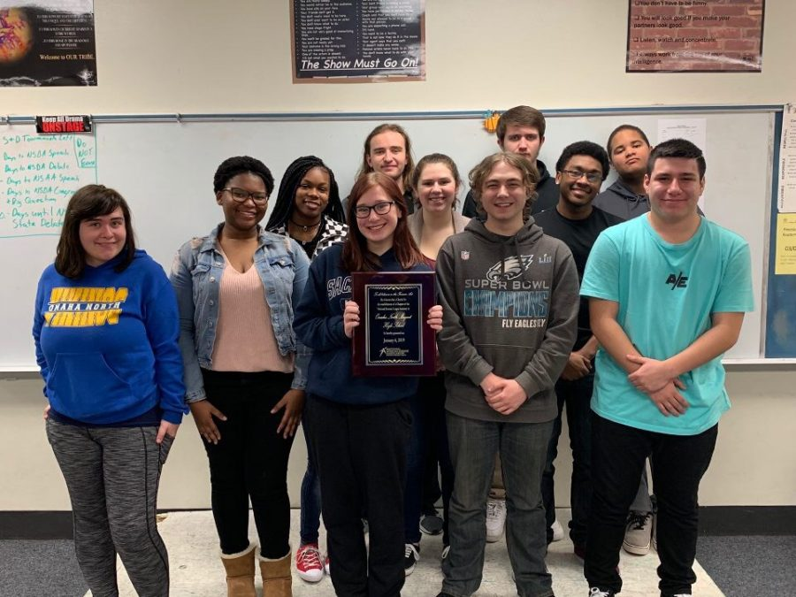 The speech and debate team poses with the plaque recognizing their membership to the National Speech and Debate Association. Photo courtesy of Michael Brown