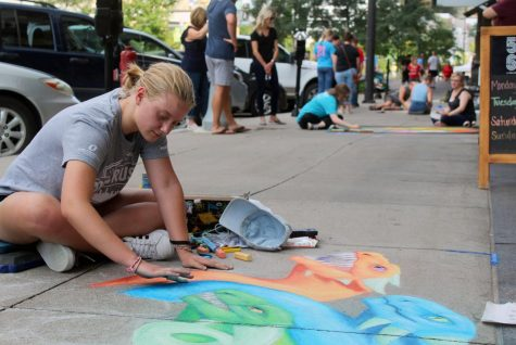 Emily Quackenbush blends colors together on her artwork for the chalk drawing competition at Midtown Crossing on Saturday, September 14. Quackenbush has been drawing since elementary school and uses it as a form of self-expression.